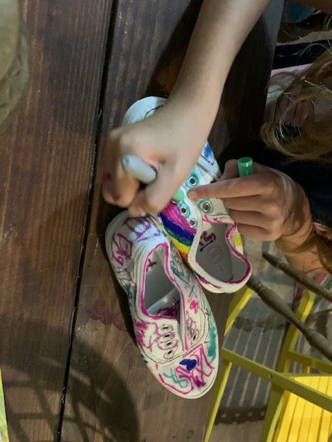 Kids under the full moon color white canvas shoes with permeant markers, then a tie-dye effect when alcohol is applied.